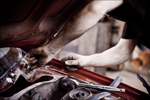 мастер ремонтирует автомобиль