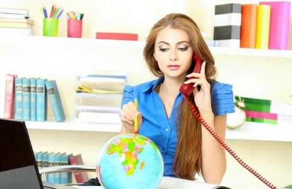 Девушка разговаривает по телефону, при этом изучает глобус