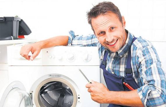 ремонтник с отверткой в руках возле стиральной машины