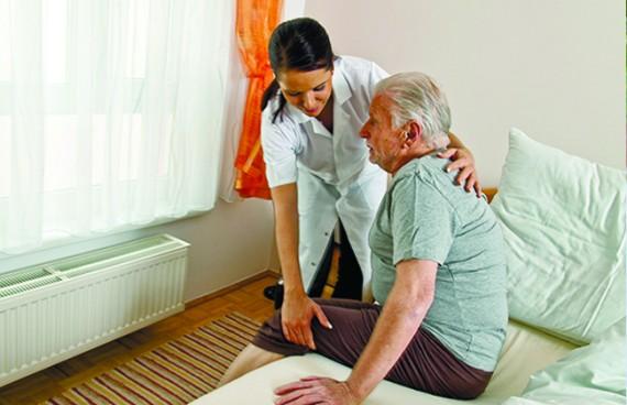 медсестра помогает дедушке встать с кровати