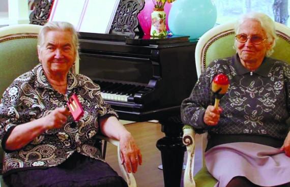 бабушки сидят в креслах и играют на музыкальных инструментах