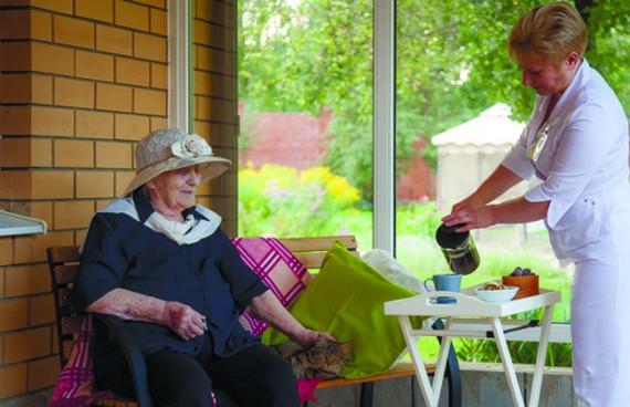 женщина в халате наливает чай пожилой бабушке