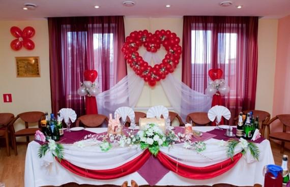 Банкетный зал украшен для свадьбы шарами и тканью