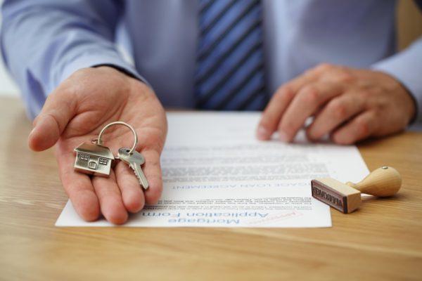 Изображение - О периоде оплаты налога с продажи квартиры в 2019 году Person-holding-a-key-and-mortgage-application-form-e1553297199441