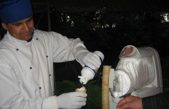 Продавец накладывает сироп на мороженое